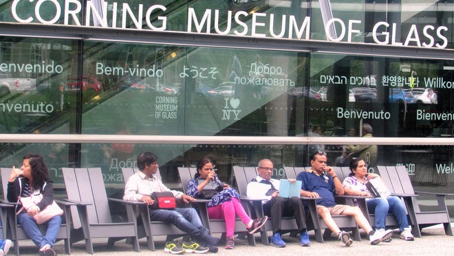Visitors sit outside the Corning Museum of Glass. The museum has seen a surge in visitors since it opened its new Contemporary Art + Design Wing in 2015.
