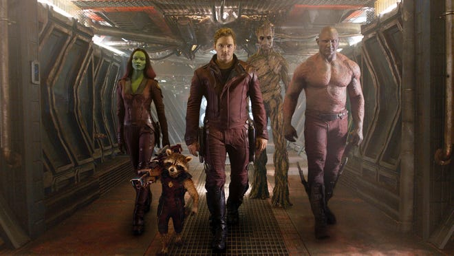 """This image released by Disney - Marvel shows, from left, Zoe Saldana, the character Rocket Racoon, voiced by Bradley Cooper, Chris Pratt, the character Groot, voiced by Vin Diesel and Dave Bautista in a scene from """"Guardians of the Galaxy."""" The movie releases on Friday, Aug. 1, 2014."""