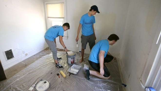 University of Rochester first-year students (from left) Edward Cho, Sean Kilcullen and Steven Spiewak, recently participated in Wilson Day, an annual event that promotes community service. They painted walls for  Rochester Refugee Resettlement Services.