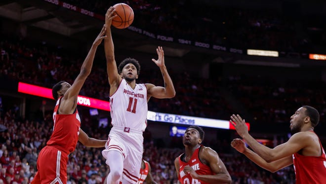 Wisconsin's Jordan Hill shoots between Ohio State's C.J. Jackson (left) and Andre Wesson during a game last season.