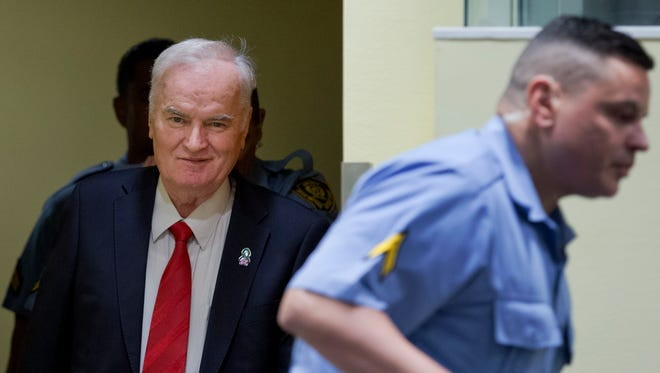 Bosnian Serb military chief Ratko Mladic, left, enters the Yugoslav War Crimes Tribunal in The Hague, Netherlands, Wednesday, to hear the verdict in his genocide trial. Mladic's trial is the last major case for the Netherlands-based tribunal for former Yugoslavia, which was set up in 1993 to prosecute those most responsible for the worst carnage in Europe since World War II.