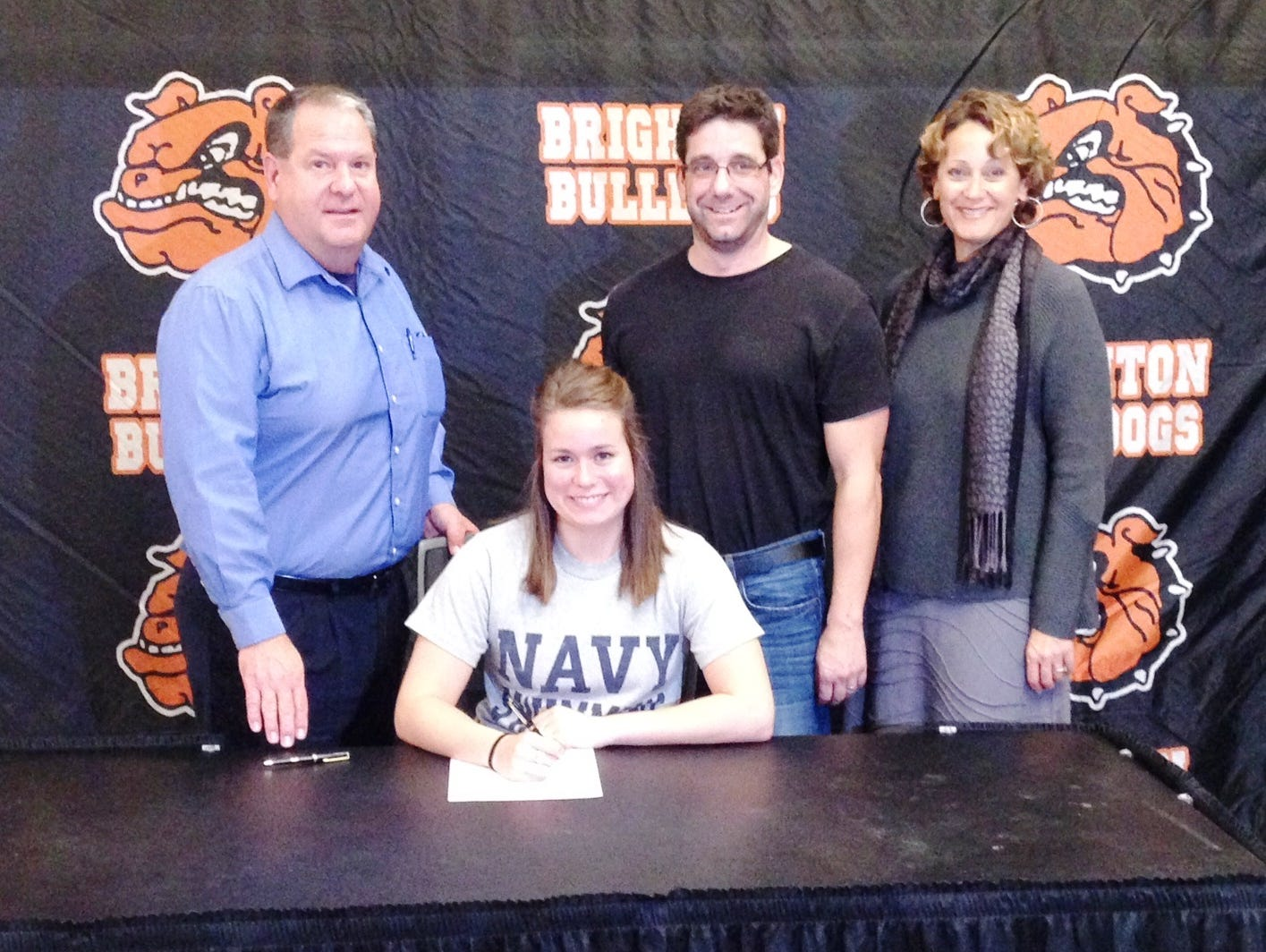 Brighton's McKenna Resconich will attend Navy next year. She's pictured here signing next to her coach Jason Black, immediate right, her dad Lou, left, and her mom Kim, right.