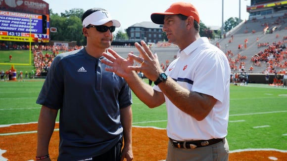 Troy head coach Neal Brown, left, speaks with Clemson