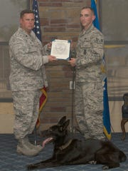 Vulkan, military working dog for the 49th Security Forces Squadron, receives a certificate of appreciation during his retirement ceremony at Holloman Air Force Base, N.M., July 27, 2018. Vulkan contributed to securing and defending 17,000 personnel that live and work on Holloman. (U.S. Air Force photo by Airman Kindra Stewart)