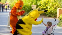 Pikachu and Charmander greet Phoebe Hills, 2, of Tempe,