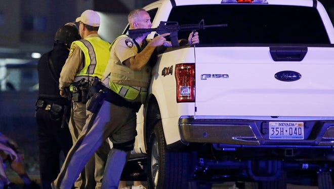 A police officer takes cover behind a truck at the scene of a shooting near the Mandalay Bay resort and casino on the Las Vegas Strip, Sunday, Oct. 1 in Las Vegas.