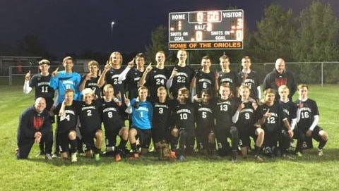 Members of the Marshall boys soccer team celebrate their Division 2 district championship victory over Charlotte on Saturday.