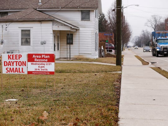 Keep Dayton Small and Area Plan Rezone meeting signs are scattrered across lawns Wednesday, February 21, 2018, in Dayton.