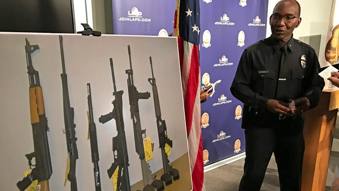 Los Angeles Police Cmdr. Horace Frank, right, shows a photo of multiple weapons found in the home of a man charged with making terrorist threats to the Islamic Center of Southern California, during a police news conference Tuesday, Oct. 25, 2016 in Los Angeles. Mark Lucian Feigin was arrested last week on the charge, which has been designated as a hate crime, according to authorities. Feigin, 40, has been released on bail. Police say Feigin first called the Islamic center Sept. 19 and left a hate-filled voicemail. The next day, they say, he called and threatened to kill people at the center.