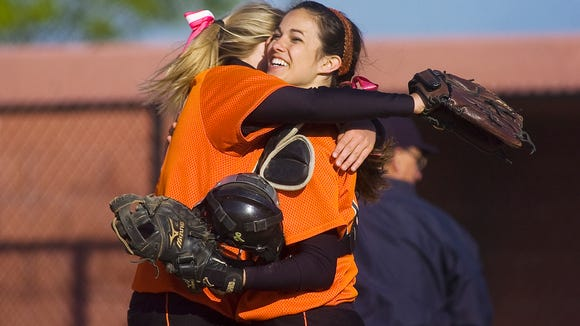 Central York softball players embrace after beating Delone Catholic to win the YAIAA tournament title Monday.