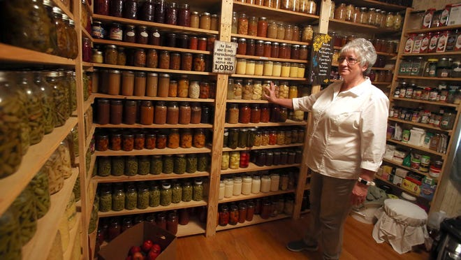 Kathy Porter looks through her room of canned goods.