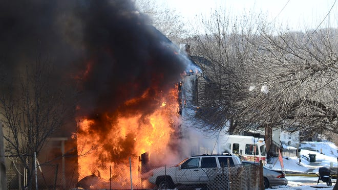 Flames engulf a 703 Fourth Ave. N home Sunday in Fort Dodge. An adult and two children are unaccounted for and four victims were transported to Trinity Regional Medical Center.