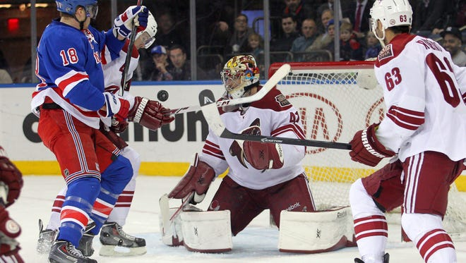 Mar 24, 2014; New York Rangers defenseman Marc Staal (18) and Phoenix Coyotes defenseman Zbynek Michalek (4) fight for a loose puck in front of Phoenix Coyotes goalie Mike Smith (41) during the second period of a game at Madison Square Garden.