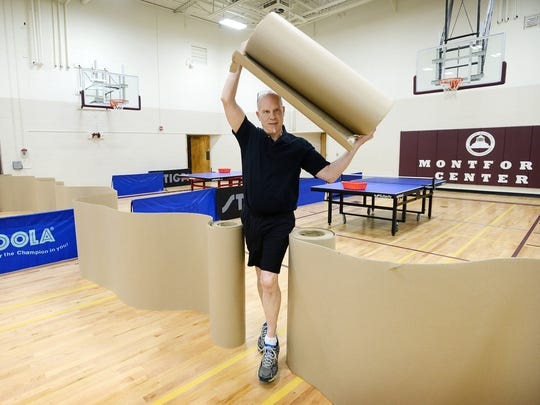 """Jim Mijanovich carries a roll of barrier material across the gym of the Montford Recreation Center as he helps set up for open play with the Asheville Table Tennis Club on Monday. Mijanovich has been coming to play with the club since November after playing in friends' garages. """"The folks here have been really generous — they don't mind beating me at all,"""" he joked."""