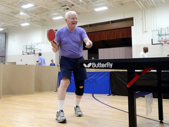 """Burm Snart prepares to serve as he takes on an opponent during an open play night with the Asheville Table Tennis Club at the Montford Recreation Center on Monday. """"It's the absolute best mental and physical exercise in the world,"""" Snart said of table tennis, noting it is low impact and may even help ward off Alzheimer's disease."""
