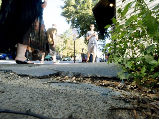 Pedestrians walk past cracked and uneven sidewalk along Broadway between College and Walnut streets Wednesday.