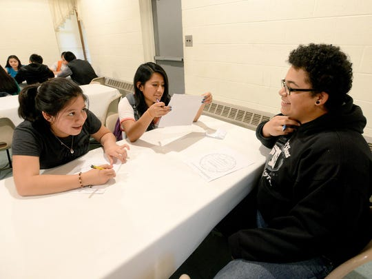 Jeanette Quituizaca, 13, left, and Cristina Felipe, 15, get help with a worksheet from mentor Taylor Lawson during a meeting of M.A.N.O.S., a Latino outreach program at Emma United Methodist Church in April. The program, which stands for Mentoring And Nurturing Our Students, has college age mentors provide social opportunities, leadership development, academic support and college preparation assistance to local high school students. Children First / Communities in Schools sponsors the program and provides additional assistance to the participants' parents.