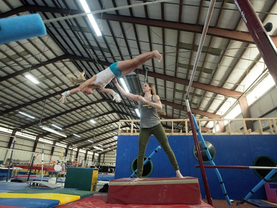 Asheville Community Movement owner Becca Hall spots Catherine Rehm, 10, as she works on a bar routine at the gymnastics studio on Tuesday, Sept. 23, 2015. The business is housed in a 40,000 square-foot warehouse on Riverside Drive.