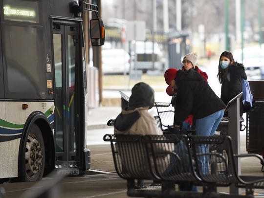 A woman wears a mask while waiting to board a bus with others at the Centro Transit Hub on Tuesday, March 17, 2020 in downtown Utica.