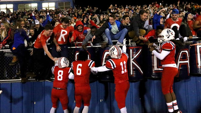 Oakland players celebrate with the crowd as the Patriots defeated Maryville 23-7 to advance to the Class 6A state final.