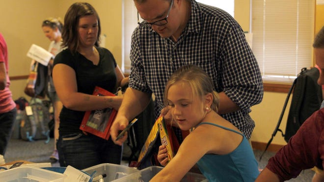 Southeast Polk school board candidate Adam Krell and his daughter, Evelyn, pack backpacks for students in need .