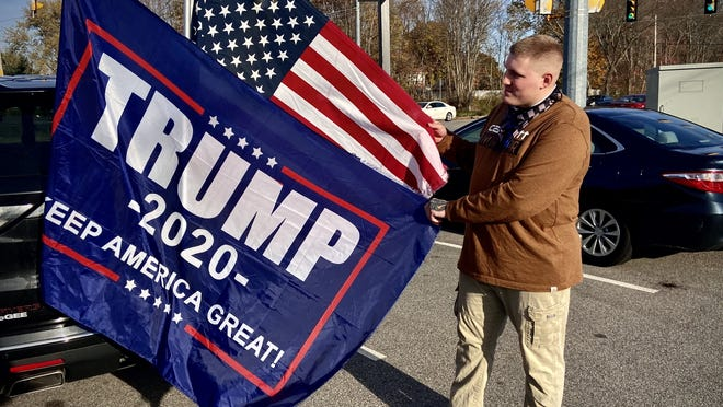 Trump supporter Justin Green is seen here Saturday in the parking lot of the New England for Donald Trump retail store in Somerset.  Herald News photo by Charles Winokoor