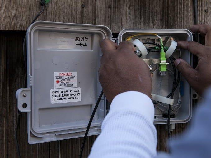 Gerron Diamond, a Google Fiber broadband technician, installs Google Fiber network at the home of customer Becki Sherwood in Kansas City, Kansas, U.S., in November 2012.