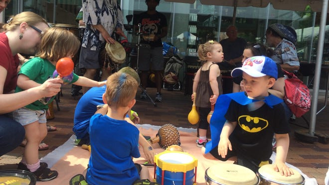 The caped Liam Gilroy, 4, drums along to the Yahoo Drummers with some bongos at the Iowa Arts Festival on Saturday, June 6.