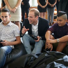 VALLETTA, MALTA - SEPTEMBER 21:  Prince William, Duke of Cambridge plays a games console with young people as he visits an Access Centre for young people called Agenzija Appogg during an official visit to Malta on September 21, 2014 in Valletta, Malta.
