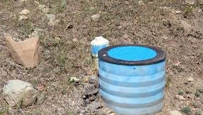 A blue lidded shaft marks an automated water meter in Ruidoso.
