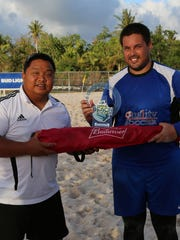 Quality Distributors FC's goalkeeper, Brett Maluwelmeng, poses with the 2016 Land Shark Beach Soccer League Golden Glove trophy, presented by Guam Football Association men's administrator Samuel San Gil, in an awards ceremony following the league's championship match Sunday at the GFA National Training Center beach soccer court.