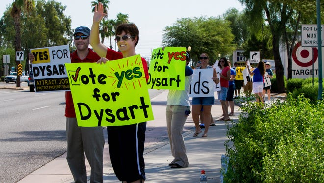 Dr. Steve and Kara Poling try to generate support for Dysart Unified School District on Bell Road in Surprise on Sept. 12, 2015. Dr. Poling is the assistant superintendent for the district, but he attended the event in an unofficial capacity as the parent of a Dysart student. The Dysart Unified School District is trying to generate support for an upcoming override, which if lost, will result in a $6 million cut.