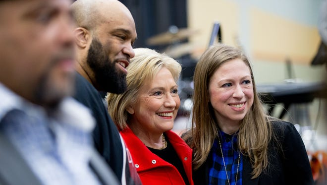 Democratic presidential candidate Hillary Clinton, center, and her daughter Chelsea Clinton, right, pose for a photograph with visitors to the African American Festival, I'll Make Me a World Celebration Day at the Iowa Events Center in Des Moines, Iowa, Saturday, Jan. 30, 2016.