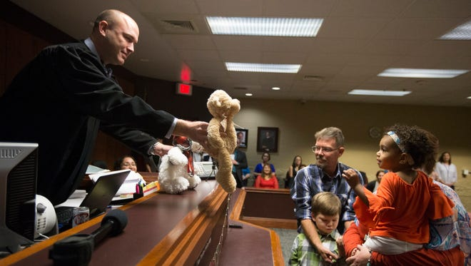 County Court at Law 5 Judge Timothy McCoy hands stuffed animals to children after making their adoptions official.