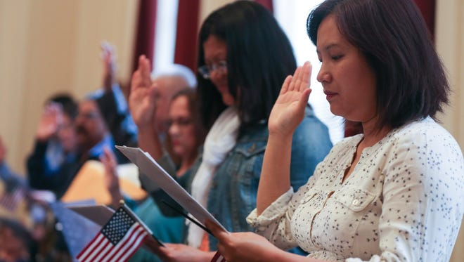 Iang Par, right, and other applicants raise their hands for the oath during the naturalization ceremony on June 1, at the United State District Court.