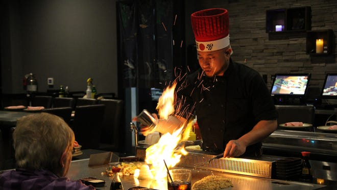 "A chef at Nagoya Japanese Steakhouse & Sushi ignites a tower of onions for the popular ""onion volcano"" trick."