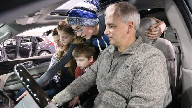 Cary Stoltz of Eagle (right) and his family - from front to back, Caden age 4, Keagan age 13, Addison age 9 and his wife Rebecca Stoltz - look over the navigation and entertainment screens on a new 2016 Buick Enclave SUV at the 2016 Greater Milwaukee Auto Show.