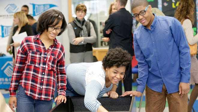 Mary Ryan Boys & Girls Club members E'Zohn Gathings (left), her sister, Charlysse Baker, and their brother, Charles Baker, play a game of carpet bowling at the newly reopened club in Sherman Park.