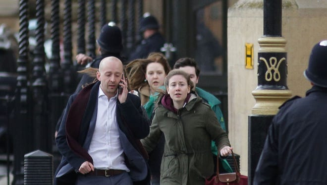 People leave after being evacuated from the Houses of Parliament in central London.