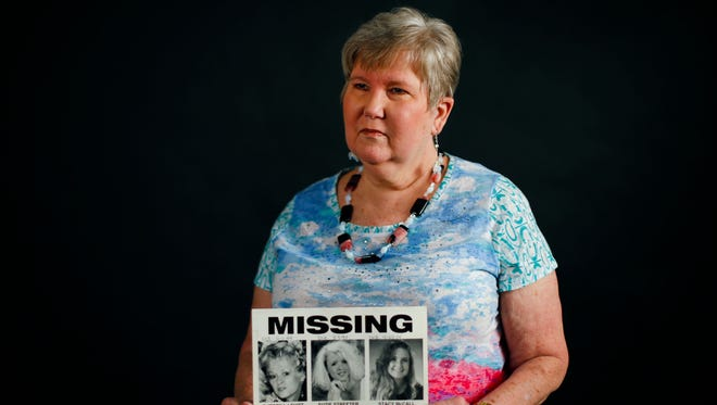 Janis McCall, the mother of Stacy McCall, holds a missing poster of the three missing women.