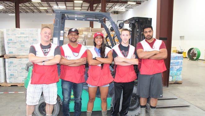 Red Horse airmen David Geaney, Paul Brooks, Heidi Agustin-Dominguez, Greg Callaham and Billy Suai helped build a Red Cross supply center from the ground up in Houston following Hurricane Harvey. Backed by teams from Maryland, they were able to get three trucks loaded with Red Cross supplies out the door and into neighborhoods every 20 minutes.  Photo courtesy of Jim McIntyre/American Red Cross