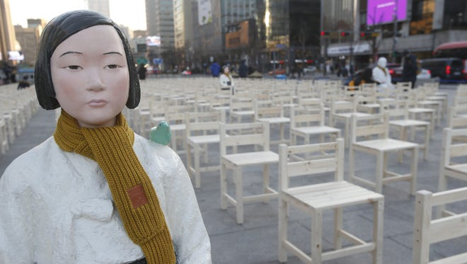 Girl and grandmother statues symbolizing 'comfort women' sit on chairs placed at Gwanghwamun Square in a performance themed 'A Promise Inscribed on an Empty Chair' after finishing this year's final weekly rally in front of the Japanese Embassy in downtown Seoul, South Korea, Dec. 17, 2017, calling for Japan's apology for its army's sexual enslavement of hundreds of thousands of Korean women during World War II.