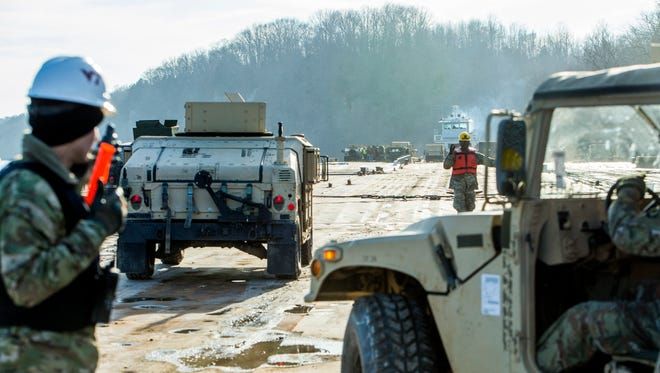 Soldiers direct vehicles while loading a barge on Feb. 12, 2018.