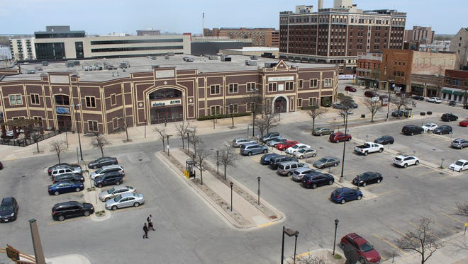 Green Bay's Redevelopment Authority is seeking proposals for  a mixed-use building on the site of the Adams Street parking lot. The request requires plans to eliminate no more than 21 of the lot's 121 parking spaces and leave Packers Heritage Trail Plaza, lower left, untouched.