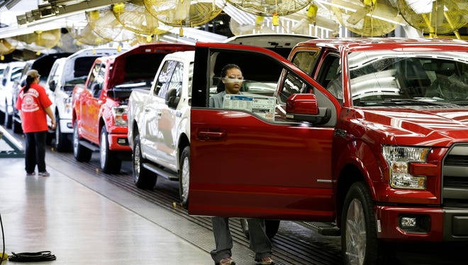 In this March 13, 2015 photo, workers inspect new 2015 aluminum-alloy body Ford F-150 trucks at the company's Kansas City Assembly Plant in Claycomo, Mo.