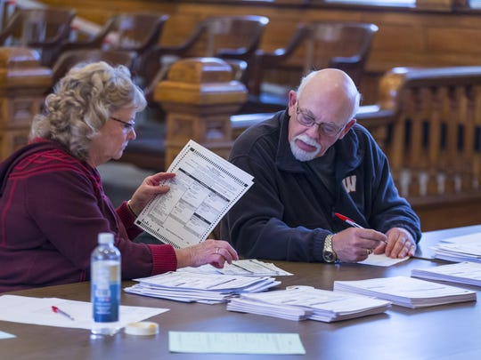 Tabulators hand count ballots inside the Green County Courthouse in Monroe as part of the recount in Wisconsin of the presidential race.