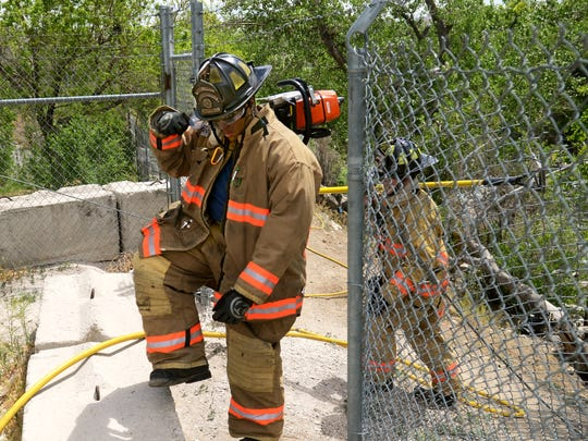 Two firefighters walk the through a fence back to a fire truck after putting out a smoldering blaze that sparked near a homeless camp Tuesday morning along the Truckee River just east of downtown Reno. Crews had responded to a call of a fire and a possible propane explosion across from the Reno Gazette-Journal.