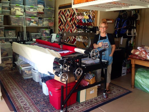 Cindy Burke has set out to complete a labor of love: sewing 150 quilts for her stepson's army battalion. Here she stands with the machine she used.