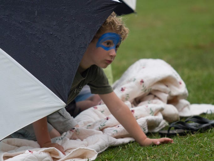 Wyatt Reynolds, 5, of Bonita Springs peers out from his umbrella while listening to the Caribbean Chillers at the 15th Annual Celebrate Bonita event at Riverside Park in Bonita Springs on Saturday. Despite the rain many turned out to see the live music and eat from the many food vendors.