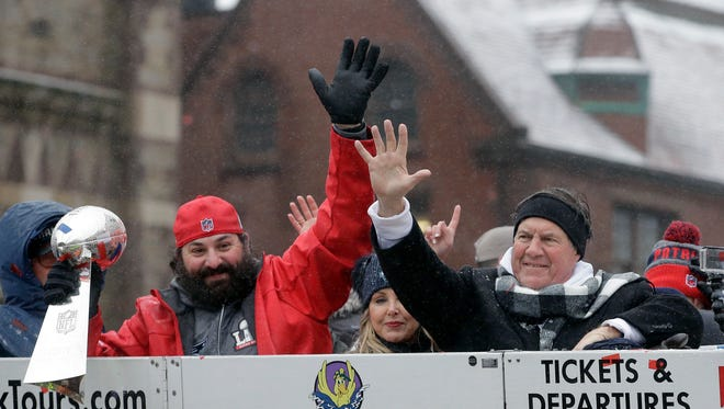 Patriots defensive coordinator Matt Patricia holds the Super Bowl trophy as he and coach Bill Belichick wave during a parade Feb. 7, 2017 in Boston to celebrate their 34-28 win over the Falcons in Super Bowl 51.